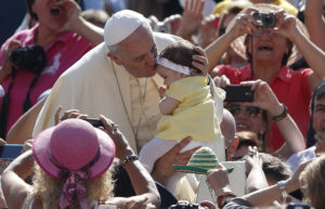Pope Francis kisses a baby girl as he arrives to lead his general audience in St. Peter's Square at the Vatican May 13. (CNS photo/Paul Haring) See POPE-AUDIENCE May 13, 2015.