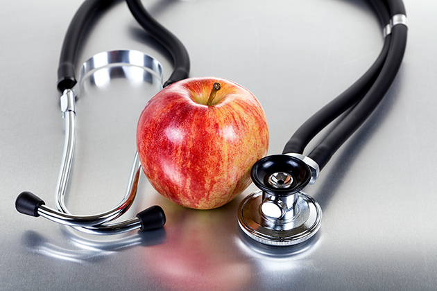 Red apple with stethoscope on stainless steel table with reflection. Good health concept.